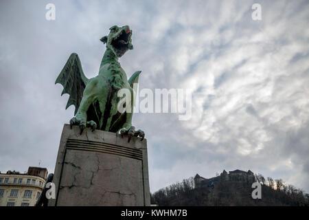 Dragon statue on Most Zmaja (Dragon bridge) in Ljubljana, capital city of Slovenia, with the Ljubljana castle in - Stock Photo