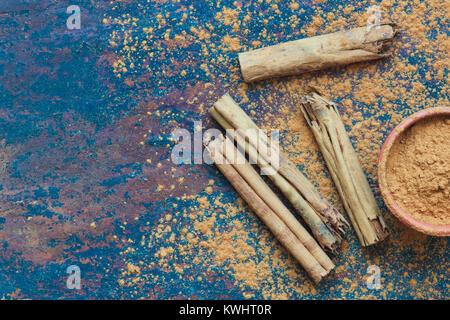 Cinnamomum verum. Cinnamon sticks and powder on slate - Stock Photo