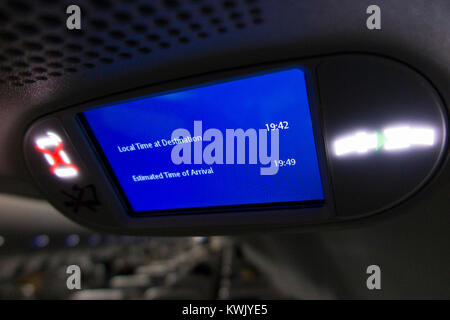 Aeroplane aircraft airplane air plane flight monitor showing travel time & distance & local time at destination - Stock Photo