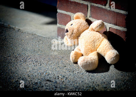 Material Teddy lies on the ground, symbolic photo childhood trauma and power, Ein Stoff-Teddy liegt auf dem Boden, - Stock Photo