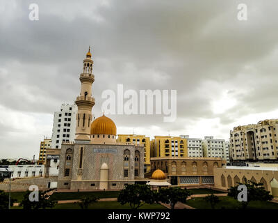 Al Khuwair Zawawi Mosque right view in front of Muscat main road in cloudy weather having beautiful sky with greenery - Stock Photo