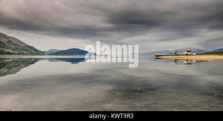 A house stands on a small peninsula, reflected in the calm sea on the shores of Loch Linnhe in the West Highlands - Stock Photo