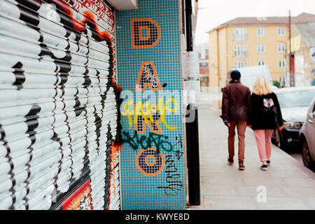 Couple walking past building with sign reading 'DARO' with graffiti on shutter in Hackney Wick, London. - Stock Photo