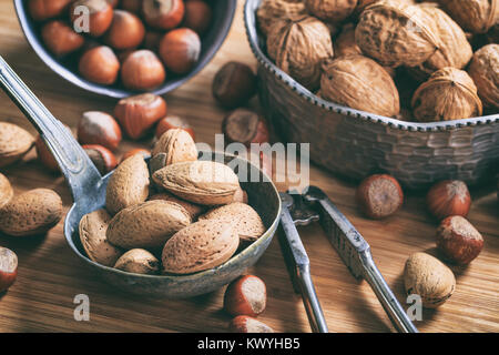 Various unpeeled nuts and a nutcracker - Stock Photo