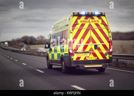 British ambulance responding to an emergency in hazardous bad weather driving conditions on a UK motorway - Stock Photo