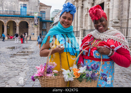 Two mulatto women with baskets of flowers and traditional costumes, in the plaza of the cathedral of Havana, Cuba - Stock Photo