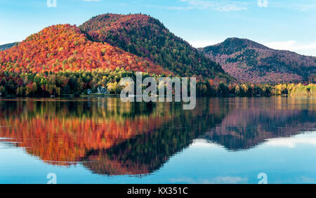 The hills covered with red maple forests are reflected in a lake in Quebec on a beautiful autumn evening - Stock Photo