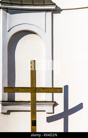 Wooden cross and church wall, Christian religious theme. Reflection of cross on wall of Catholic church on sunny - Stock Photo