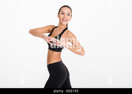 Photo of gorgeous young sports woman posing isolated over white background. Looking aside make exercises. - Stock Photo