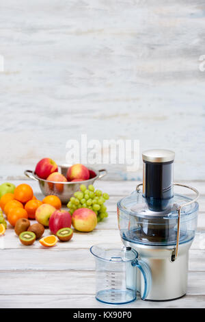 Modern electric juicer and various fruit on kitchen counter, healthy lifestyle detox concept. New year's resolution, - Stock Photo