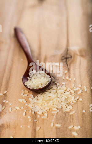 Raw long-grain steamed rice in a spoon on a wooden background. Ingredient for a healthy diet. - Stock Photo