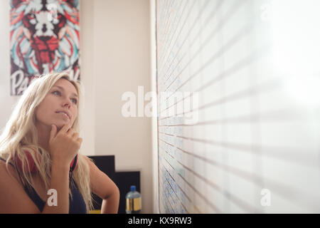 Female executive looking at whiteboard in office - Stock Photo