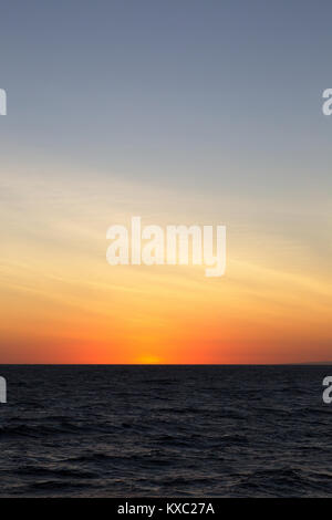 Sunset over the Pacific Ocean on the equator at the galapagos Islands. - Stock Photo