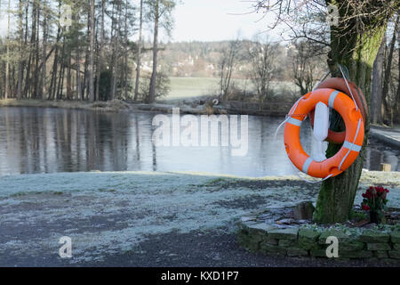 Life safety orange ring buoy at deep water private fishing lake in rural countryside - Stock Photo