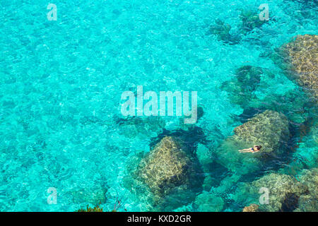 Person swimming in the emerald waters of Cala Mitjana, Menorca, Balearic Islands,  Spain, Europe - Stock Photo