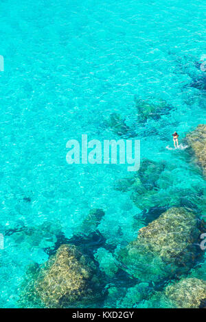 Person swimming in the emerald waters of Cala Mitjana, Menorca, Balearic Islands,  Spain, Europe - Stock Photo