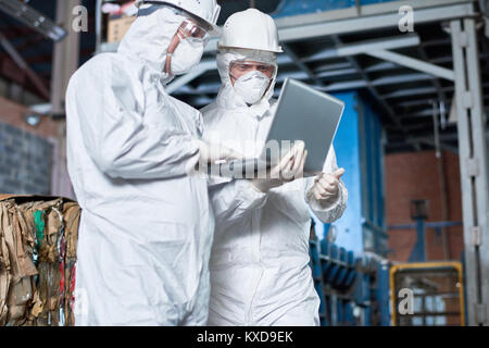 Workers in Hazmat Suits at Factory - Stock Photo