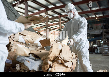 Worker in Protective Suit Sorting Cardboard at Factory - Stock Photo