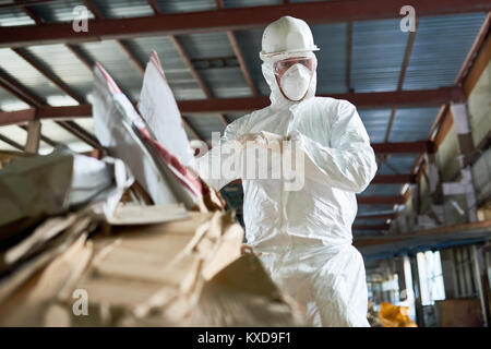 Worker in Hazmat Suit Sorting Cardboard at Recycling Plant - Stock Photo