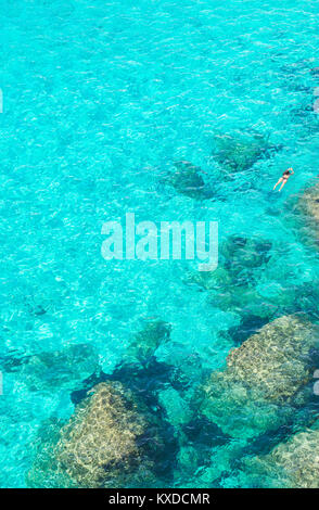 Person swimming in the emerald waters of Cala Mitjana,Menorca,Balearic Islands,Spain - Stock Photo