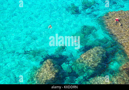People swimming in the emerald waters of Cala Mitjana,Menorca,Balearic Islands,Spain - Stock Photo