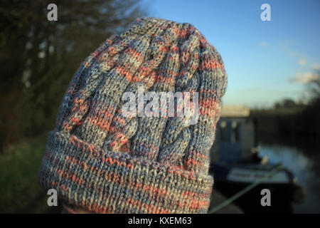 A lovely soft hand knitted adult's beanie type hat which is knitted from a yarn that has grey and pink shades with - Stock Photo
