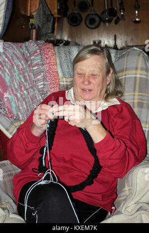 A lady concentrating on hand knitting a blanket sitting aboard a canal narrow boat. She is knitting on a circular - Stock Photo