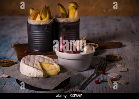 Horizontal photo of hot melted camembert cheese on paper sheet with bowl full of garlic and onions and old vintage - Stock Photo