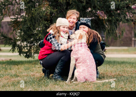 Sisters and their mother crouching to pet dog in garden - Stock Photo