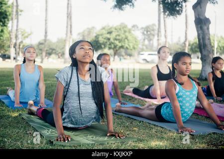 Girls and teenage schoolgirls practicing yoga upward facing dog on school playing field - Stock Photo