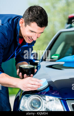 Man using an absorbent towel for drying the surface of a car - Stock Photo