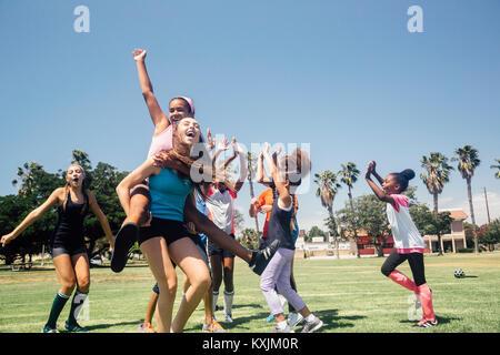 Schoolgirl soccer team celebrating on school sports field - Stock Photo