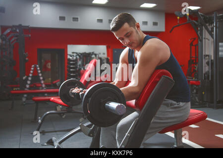 Handsome man doing biceps lifting barbell on bench in a gym - Stock Photo