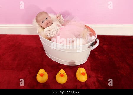 baby girl sitting in tin bath playing with ducks, happy childhood - Stock Photo