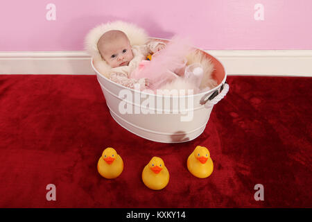 baby girl sitting in tin bath, play time - Stock Photo