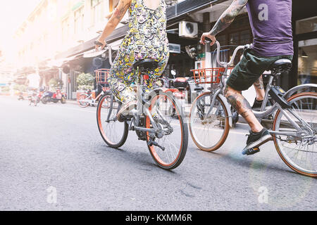 Waist down view of multi ethnic hipster couple cycling along street,Shanghai French Concession,Shanghai,China - Stock Photo