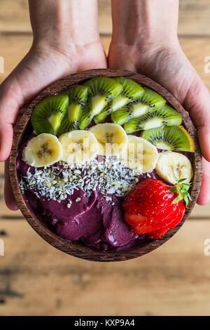 Acai bowl in hands - Bowl of acai purée with toppings of banana, kiwi, strawberry and seeds. - Stock Photo