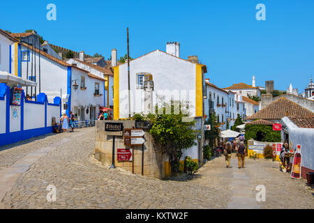Tourist walking on cobbled streets of medieval town of Odidos. Portugal - Stock Photo