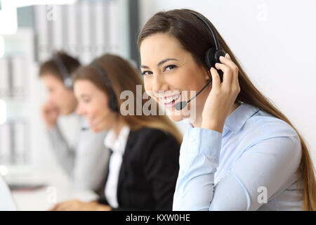 Portrait of a happy telemarketer working looking at you at call center - Stock Photo