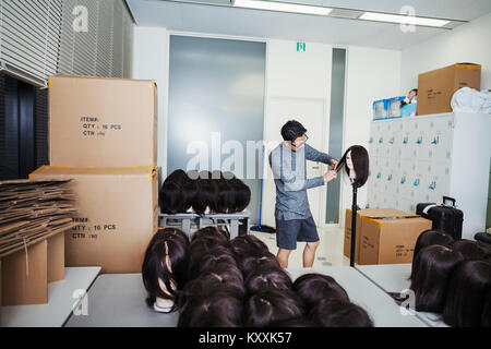 Bearded man wearing glasses standing indoors, cutting hair of brown wig on mannequin head. - Stock Photo