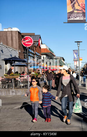 SAN FRANCISCO-FEB 22, 2014: Unidentified visitors walk along a street in historic Fisherman's Wharf, one of San - Stock Photo
