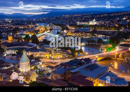 Scenic Top View Of Tbilisi, Georgia In Evening Lights Illumination. Metekhi Bridge, Surb Gevorg Church And All Famous - Stock Photo
