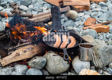 Live fire cooking juicy sausages over campfire. - Stock Photo