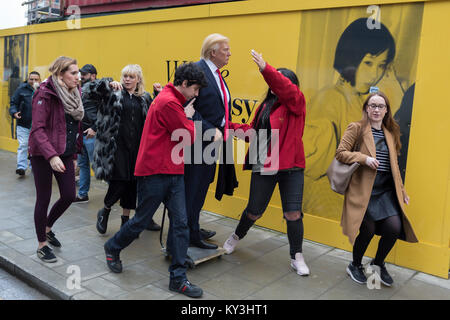 The waxwork of Donald Trump is carried to the US Embassy at Nine Elms in south London on the day when the President - Stock Photo
