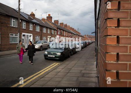 Two women crossing a road in the Golden Mile district of the city of Leicester in the English Midlands. The district - Stock Photo