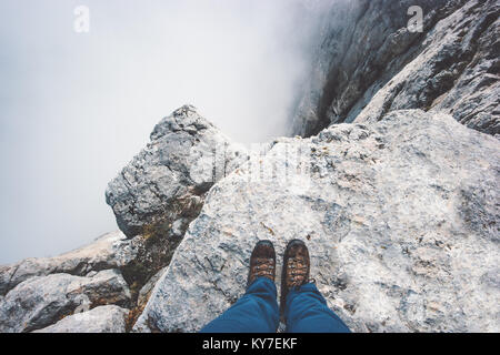 Traveler Feet boots on rocky mountain cliff over foggy clouds Travel Lifestyle success concept adventure active - Stock Photo