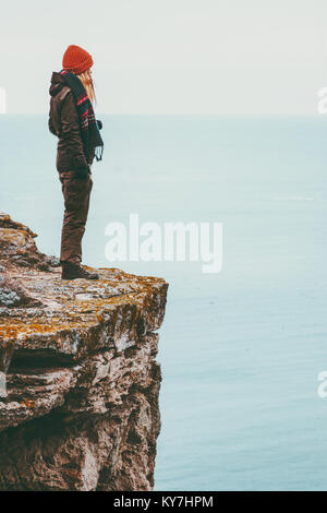 Woman alone standing on cliff edge above sea Travel Lifestyle concept Solitude melancholy emotions harmony with - Stock Photo