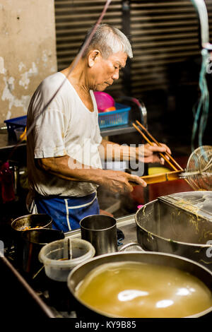 An elderly Malaysian street vendor cooking up a noodle dish on his street food stall in Melaka, Malaysia. - Stock Photo