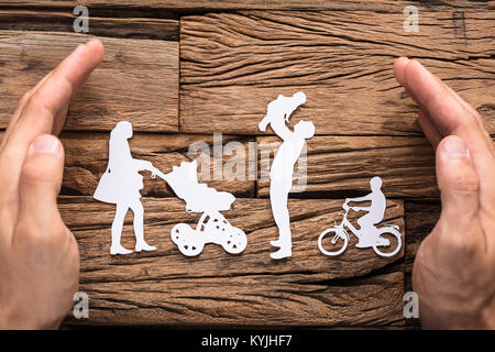 Close-up Of Hands Protecting The Family's White Paper Cut Out On Wooden Table - Stock Photo