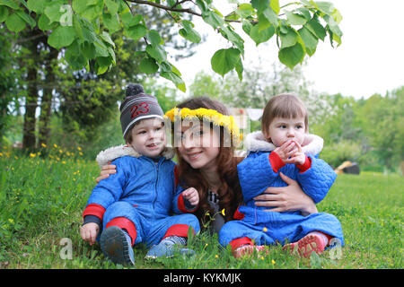 mother with young twins sitting on a green meadow in early sprin - Stock Photo